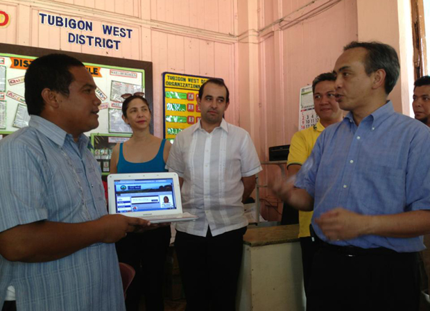 ICT Office chief Louis Casambre (right) converses with Christopher Gudia, principal of Tubigon West Central School in Bohol, as the latter shows off a computer connected to the Internet using TVWS. Also in photo is ICT Office deputy executive director Bettina Quimson (2nd from left)