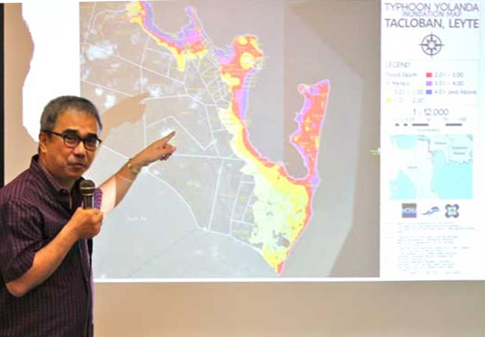 "DOST secretary Mario Montejo demonstrates the use of a hazard map, particularly in rebuilding the Yolanda-ravaged Tacloban City. The map was acquired and processed by the DOST-UP project ""Disaster Risk and Exposure Assessment for Mitigation?"
