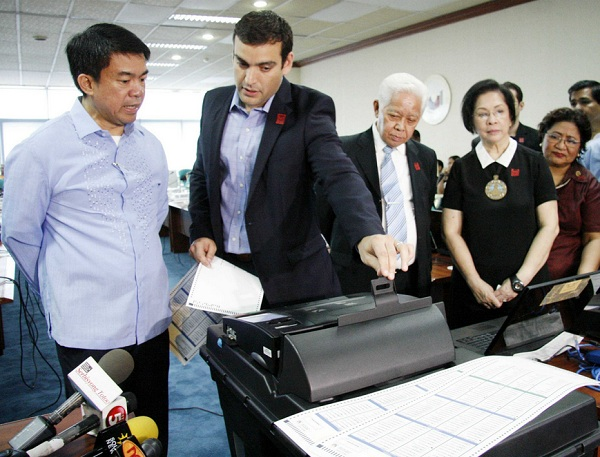 In this file photo from PNA, Sen. Koko Pimentel is seen being briefed on the PCOS machines by Smartmatic CEO Cesar Flores as Comelec chair Sixto Brillantes and PPCRV chair Henrietta de Villa look on