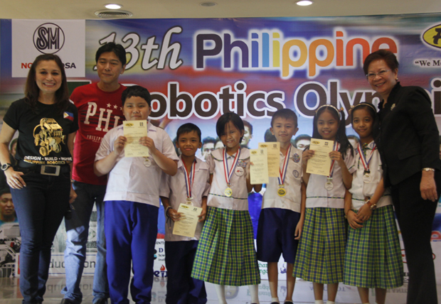 One of the winning schools flashes their medals and certificates during the awarding ceremony of the 13th PRO