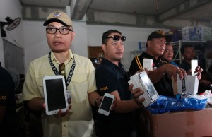 Combined operatives of the NBI, IPOPHL, Customs (NICE) Enforcement Team and the PNP-CIDG led by Ben Entico of the Bureau of Customs and Atty. Jerome Turga of IPOPHL inspect the fake smartphones and other electronic gadgets seized in raid in Binondo, Manila. Photos by Reynante Salgado