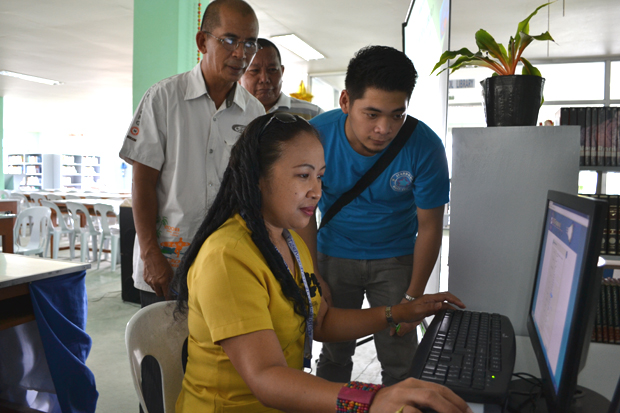 Southern Leyte State University VP for academic affairs Lorelie P. Duarte searches for some information about Typhoon Ruby in a Starbooks terminal during its formal turn over led by the DOST-STII at its Sogod, Southern Leyte campus. Also in photo are Lloyd Mandapat of DOST-STII (right) and Dr. Dominador A. Clavejo, provincial science and technology director, DOST Region 8. -- Photo by Joy M. Lazcano, DOST-STII