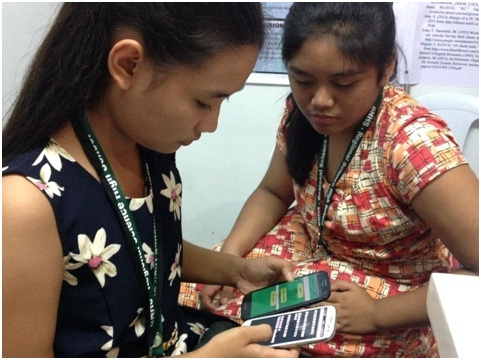 Marian Elaine Dechaves (in black) and Charmaine Galindez show how to use the app