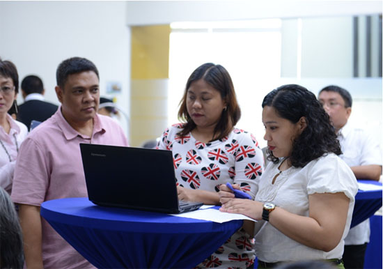 Marlo Carag of the Bureau of Trademarks (left) assists participants as they try the new eTMfile