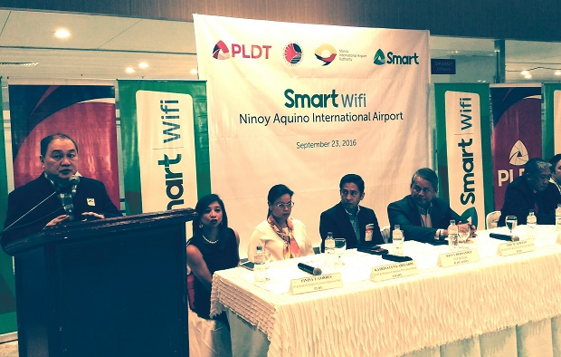 PLDT and Smart chair Manuel V. Pangilinan (left) speaks during the Friday launch of Smart WiFi's carrier-grade boost at the four terminals of NAIA. Photo also shows Transportation secretary Arthur Tugade (right) and PLDT-Smart and other government officials