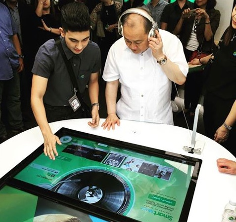 PLDT and Smart Communications chair Manny V. Pangilinan tries out the touchscreen menu at Smart's new flagship store at the SM Megamall