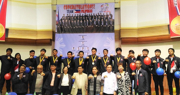 Tesda chief Gene Mamondiong (center, front row) strikes a post during the recognition rites for Filipino medalists in the Asean Skills Competition in Malaysia