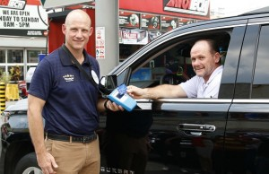Chevron and Visa executives demonstrate the contactless feature of Visa payWave, the new technological innovation at Caltex which allows cardholders to just wave their card and go