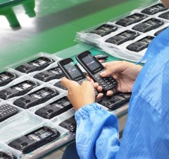 A worker boots up a pair of Starmobile UNO B208 units for inspection