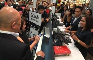Top executives of Globe Telecom and SM try out the scan-to-pay feature of GCash at the SM store in Mall of Asia